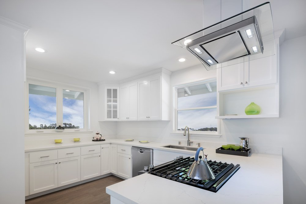 Pure white U-shaped kitchen lighted by recessed ceiling lights.