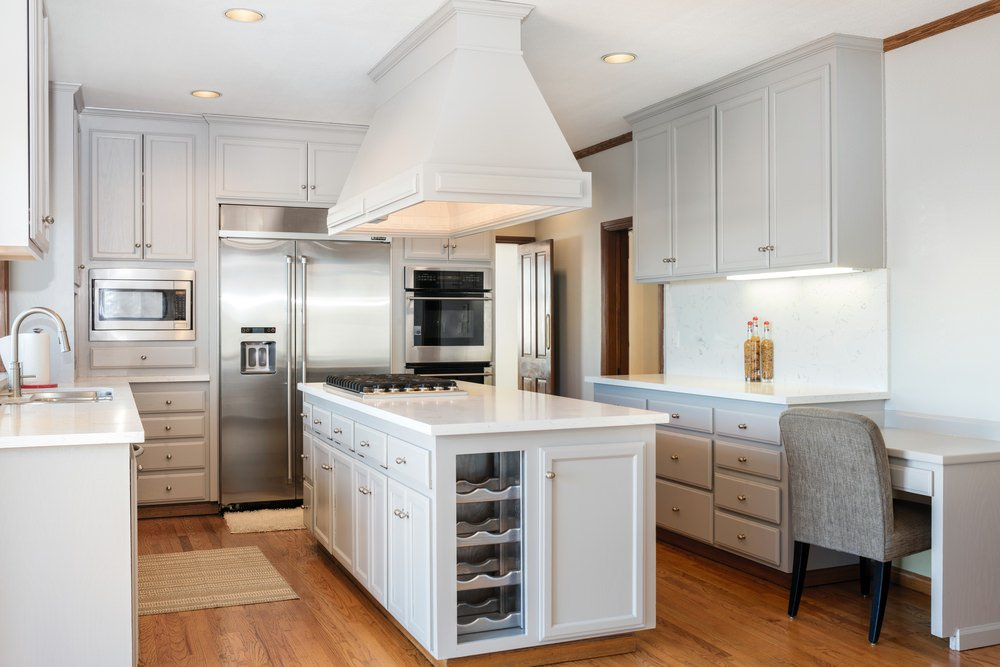U-shaped kitchen with white cabinetry, walls, counters and center island along with smooth white countertops and walnut finished hardwood flooring.