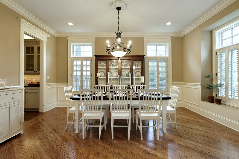 A gorgeous dining table set on top of the stylish hardwood floors and is lighted by a fabulous ceiling light. The room is surrounded by beige walls.