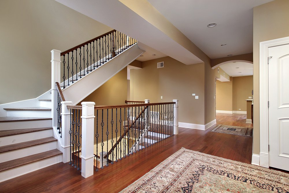 This second floor landing boasts a hardwood flooring topped by rugs. The hallways are lighted by recessed ceiling lights.