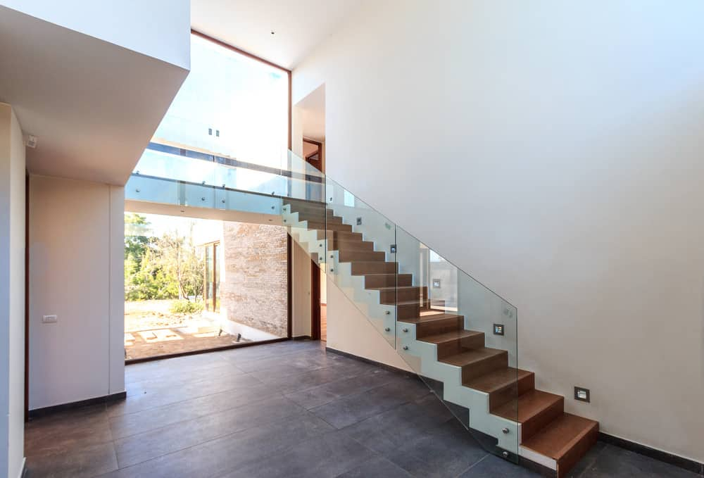 Wooden staircase framed with glass paneled railings and white stringer surrounded by white walls and a floor to ceiling window.