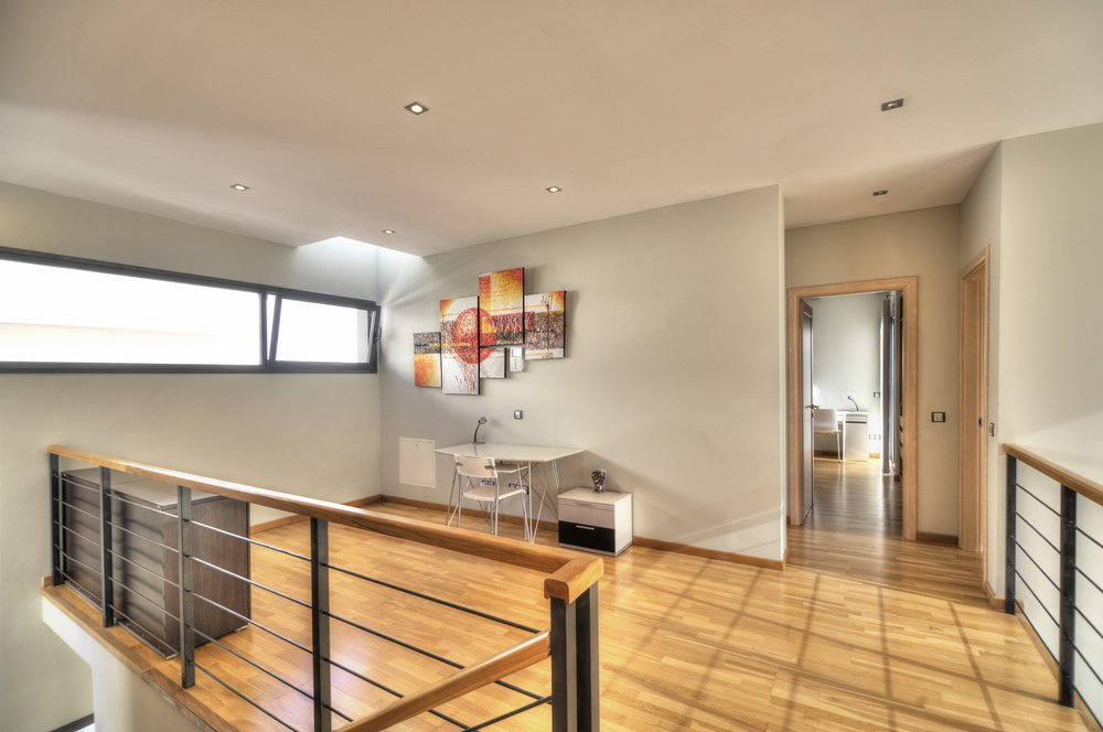 Second floor landing featuring a hardwood flooring. The staircase leads to the small home office area with a stylish wall decor lighted by recessed lights and a skylight.