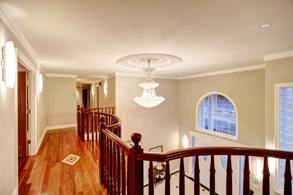 Second floor landing featuring a gorgeous hardwood flooring and railings. The hallway is lighted by charming wall lights.
