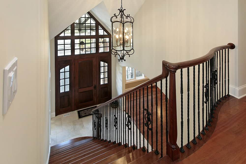 An entryway features a glass paneled wooden door that complements with the staircase fitted with ornate wrought iron spindles and illuminated by a vintage glass chandelier.