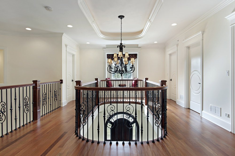 Second-floor landing featuring hardwood flooring and white walls, together with recessed lights and a charming chandelier.