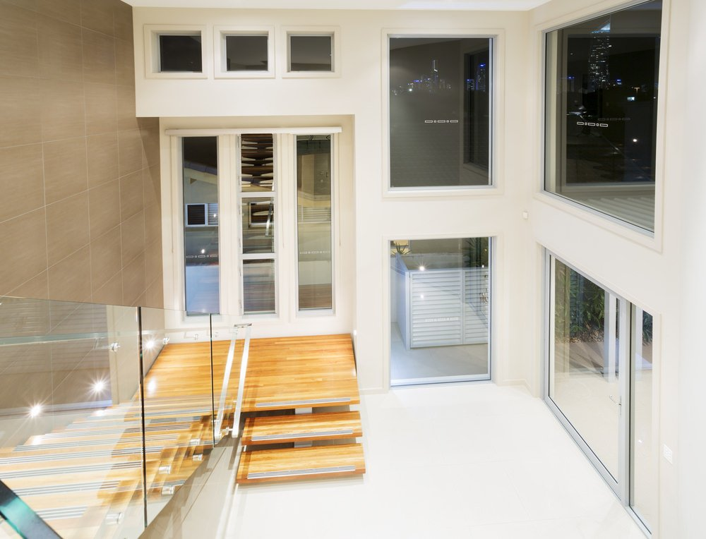 This home boasts a white walls and flooring along with glass doors and windows. The staircase leads to the home's second floor landing lighted by recessed ceiling lights.