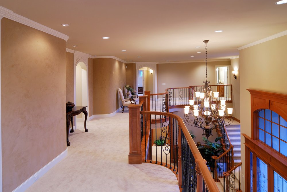 This second floor landing boasts a carpet flooring spreading throughout the home. There are seats on the side. The hallways are lighted by recessed and wall lighting.