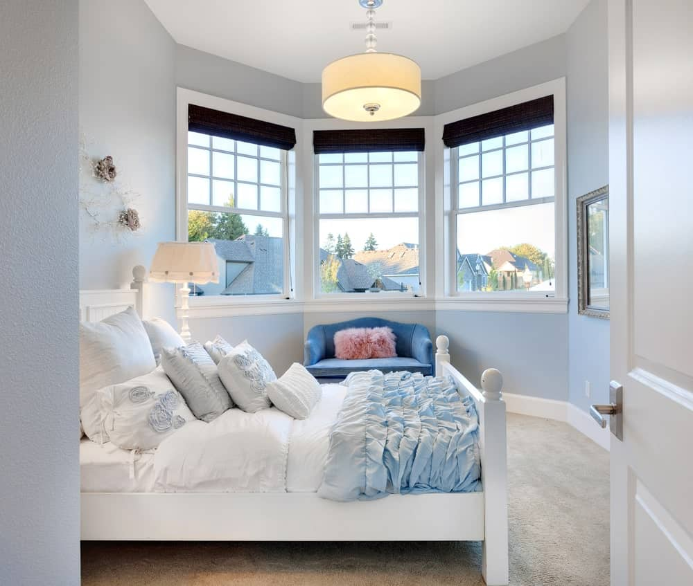 Charming bedroom with a white bed accented with ruffled blanket along with a blue couch beneath the triple pane windows covered with black roman shades.