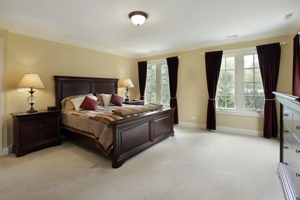 This primary bedroom is furnished with a drawer chest and a dark wood bed with matching nightstands on its sides topped with traditional table lamps.