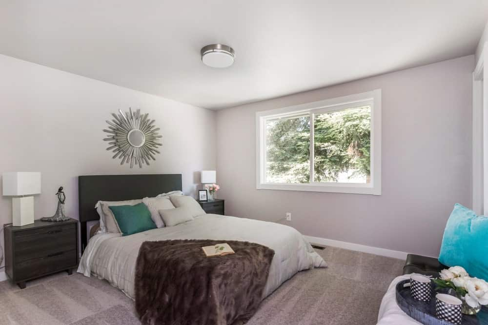A silver sunburst mirror is mounted above the black bed in this master bedroom with picture windows and carpet flooring.