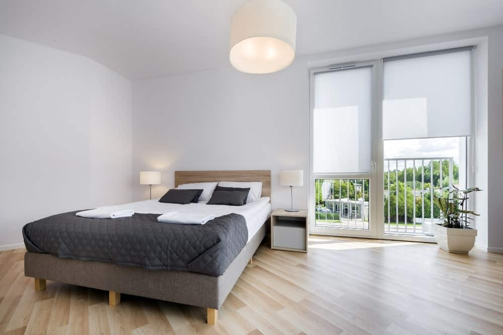 Airy primary bedroom with hardwood flooring and glass windows covered in translucent roller blinds. It includes a wooden bed and nightstands with white table lamps that match the semi-flush mount ceiling light.