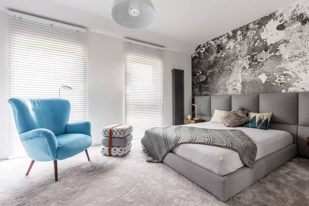 Gray primary bedroom accented with a blue wingback chair that faces the bed with a custom headboard over carpet flooring.