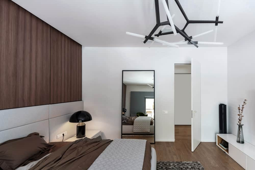 Contemporary primary bedroom offers a brown bed with gray custom headboard and nightstand topped with a black dome table lamp.