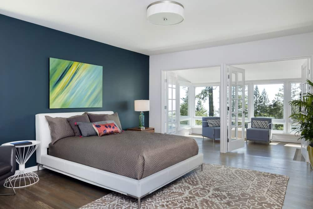 Fresh primary bedroom decorated with a lovely wall art mounted above the gray bed. It has double french doors that open to the sitting area with soft blue chairs.