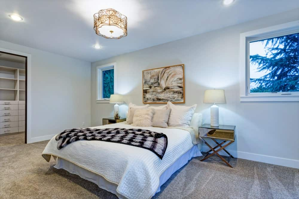 An ornate flush ceiling light illuminates this primary bedroom along with white table lamps that sit on the wooden nightstands with a white bed in the middle.