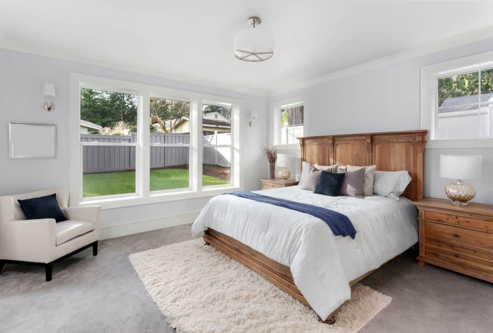 White primary bedroom with a wooden bed and nightstands topped with drum table lamps. It includes a wingback chair by the window accented with a deep blue throw pillow.