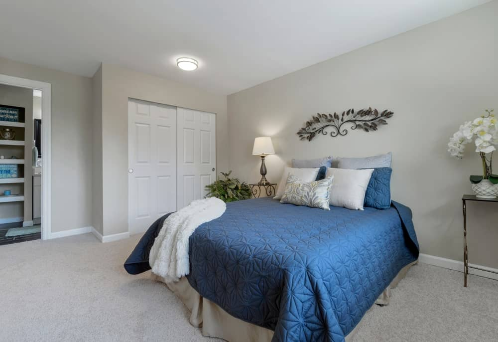 Charming primary bedroom showcases a blue bed accented with an interesting wall decor and illuminated by a table lamp and flush mount ceiling light.