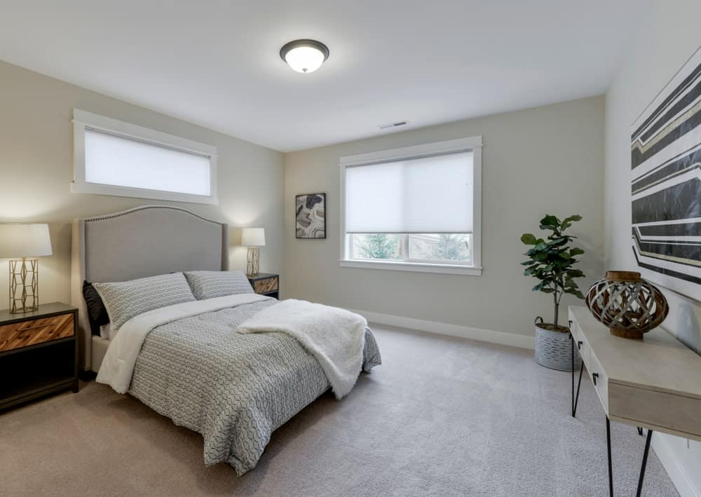 Brass table lamps illuminate this primary bedroom along with a flush mount and natural light from the glass windows covered with translucent roller blinds. It has a gray bed that faces a light wood desk topped with a lovely decor.