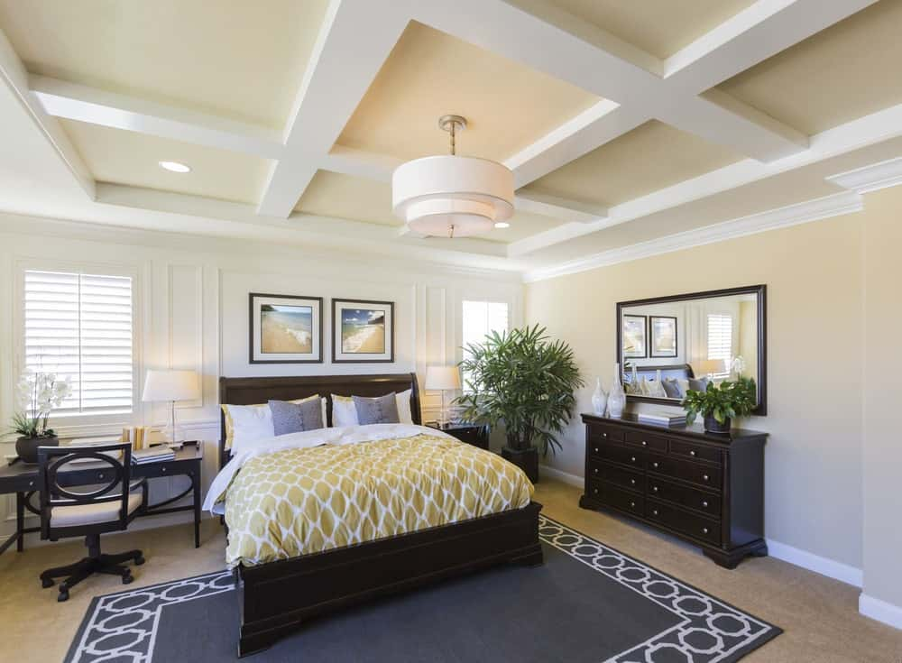 This master bedroom offers a dark wood bed dressed in yellow patterned bedding. It complements with the dresser drawer and desk that's paired with a cushioned chair.