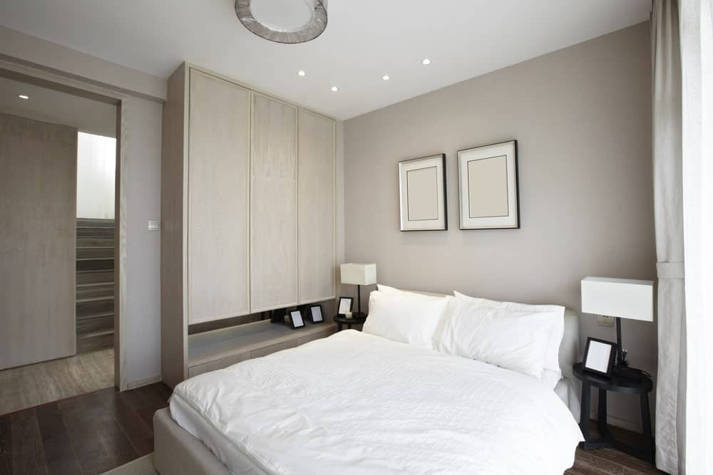 Neutral primary bedroom decorated with black framed wall arts mounted above the white bed with round nightstands on each side topped by modern table lamps.