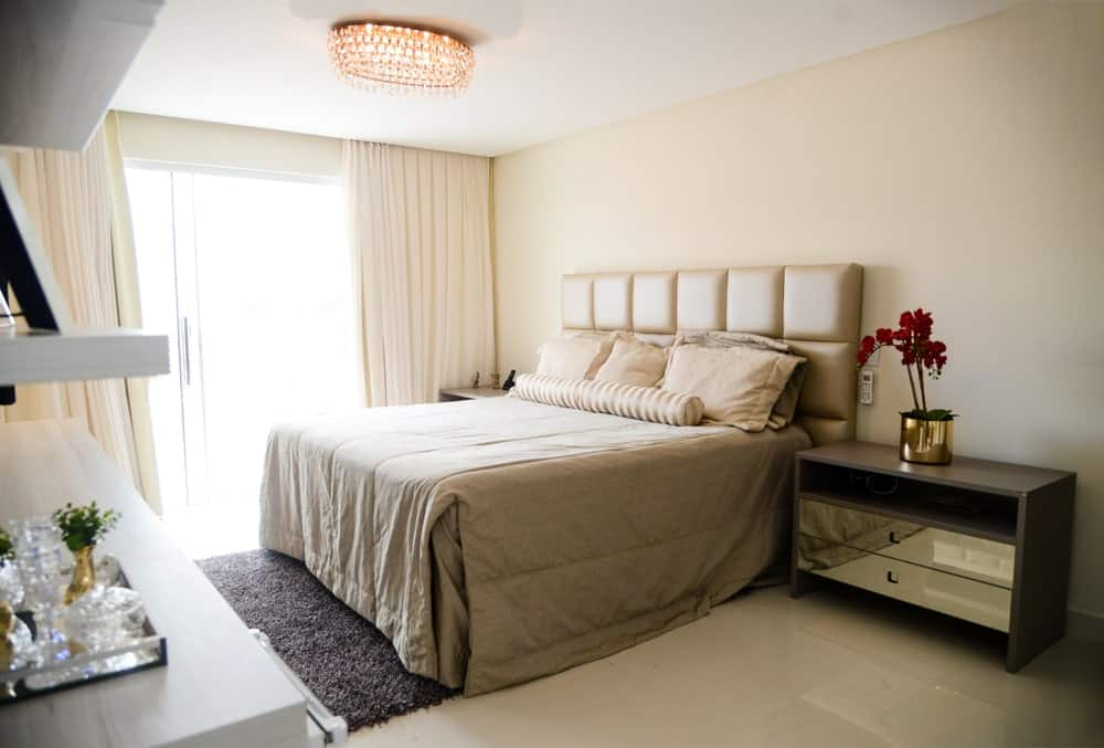 Cream primary bedroom illuminated by a fancy crystal flush light and natural light from the full height glass windows covered with draperies. It has a leather tufted bed and mirrored nightstands over glossy flooring topped by a shaggy rug.