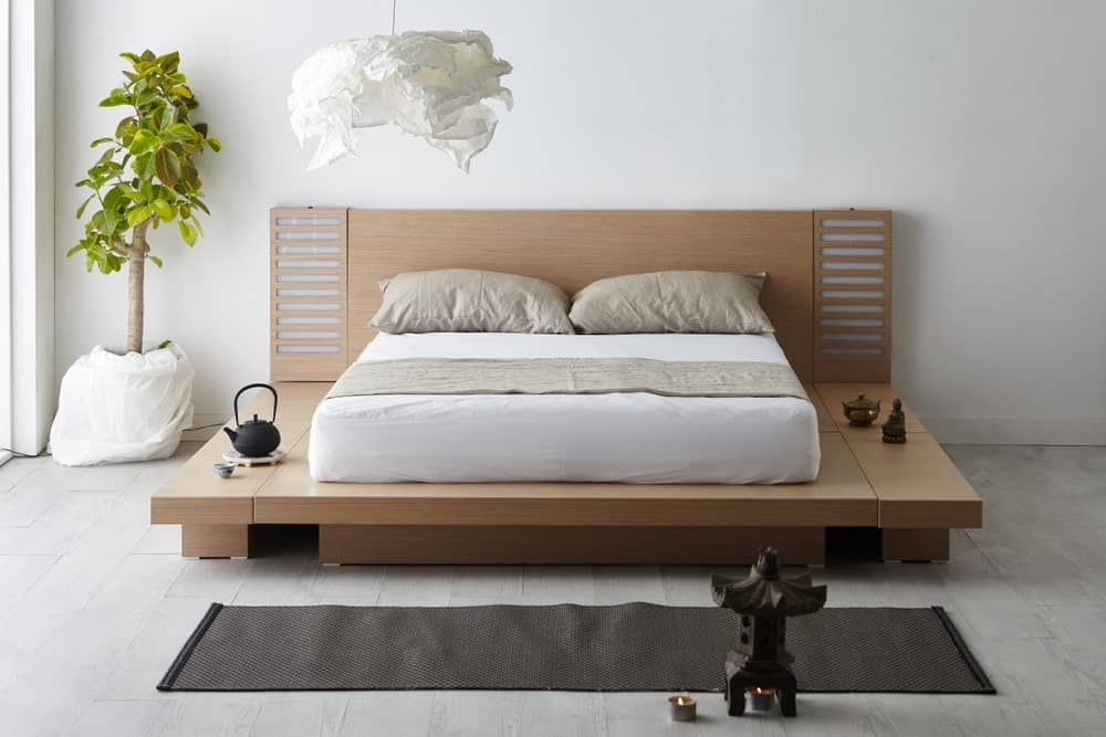 Serene primary bedroom with a platform bed accented with an indoor plant that creates a refreshing ambiance to the room. It has a modern semi-flush light and light wood flooring topped by a slim black rug.