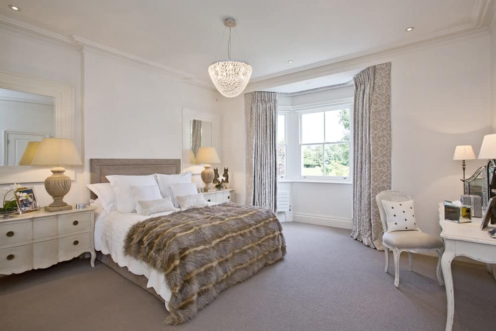 A crystal semi-flush light hangs over the beige velvet bed dressed in white bedding and fur blanket in this primary bedroom with carpet flooring.