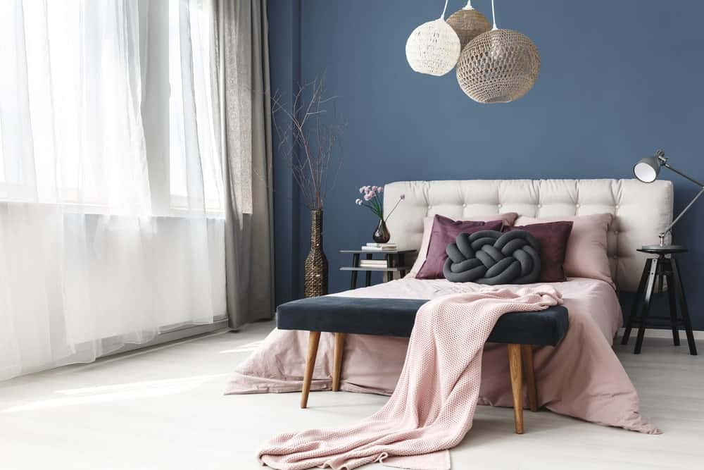 Gorgeous primary bedroom designed with a decorative twig and round semi-flush lights that hung over the pink bed with white tufted headboard.