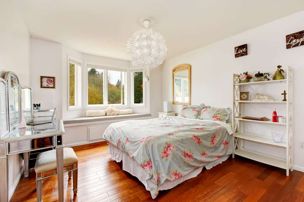 Fabulous primary bedroom illuminated by a round semi-flush light that hung over a floral bed facing the mirrored vanity with matching stool. It has a window seat nook topped with a gray cushion and white pillows.
