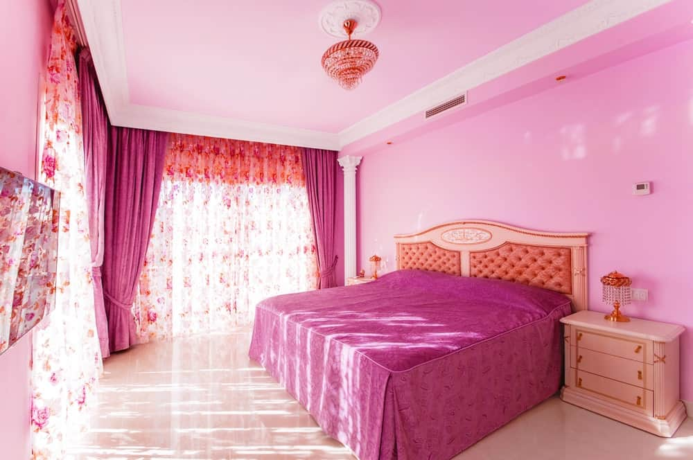 Pink primary bedroom with beige flooring and full height glass windows covered with floral curtains and magenta draperies matching with the bed cover.