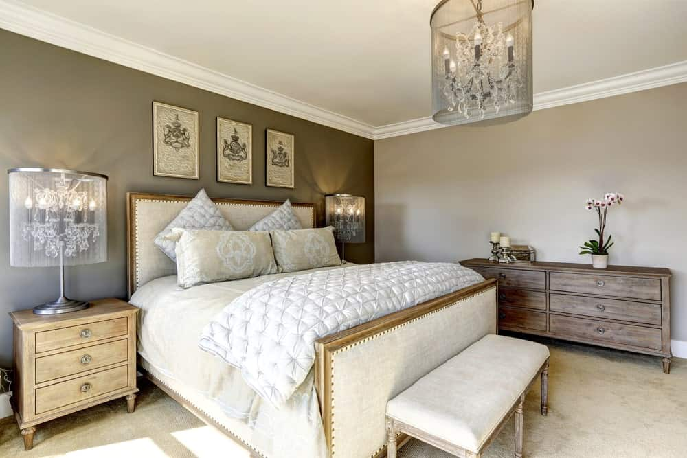 A luxurious semi flush light illuminates this primary bedroom along with matching table lamps that sit on natural wood nightstands. It has a white bed and rustic dresser drawer topped with candles and plants.