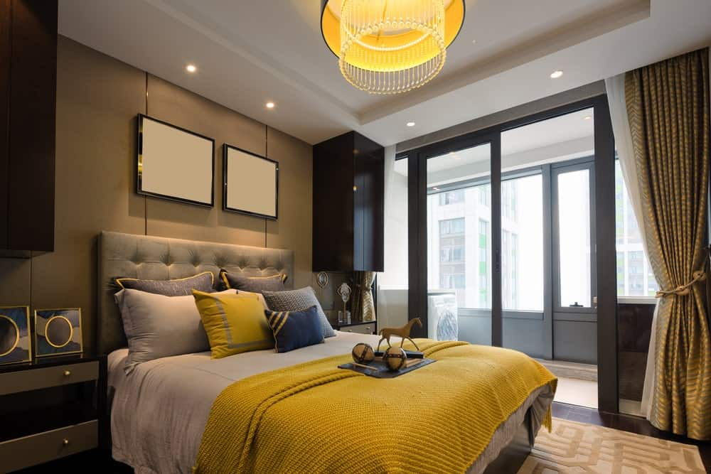 Sophisticated primary bedroom decorated with blank canvases mounted above the gray tufted bed. It is lighted by an amber semi-flush light that complements with the woven blanket.