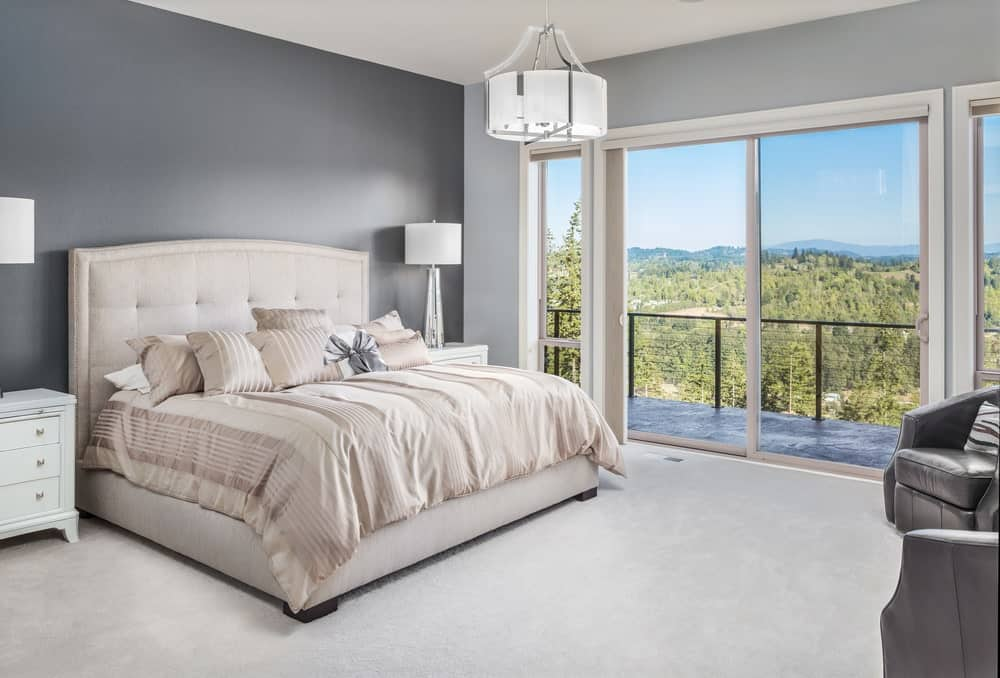 Gray primary bedroom with carpet flooring and glass sliding doors that open to the balcony with a magnificent outdoor view. It has a beige tufted bed in between white nightstands topped with sleek table lamps.