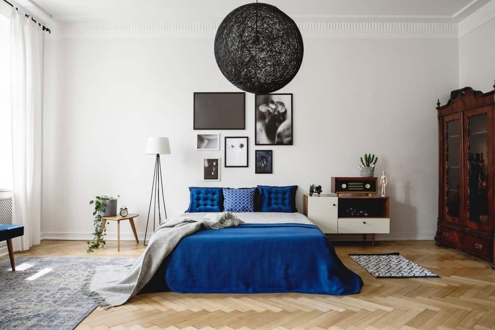 An oversized black woven semi-flush light hangs over the blue bed in this primary bedroom with herringbone wood flooring and white wall designed with gallery frames.