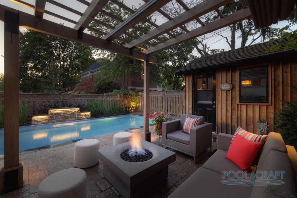 A rectangular swimming pool showcases a stacked stone waterfall and a poolside cabana with taupe sectional and armchair accented with red and striped pillows. It includes a concrete fire pit and white stools.