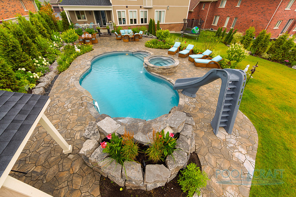 An aerial view of this home's beautiful garden area featuring a custom pool with a slide and a jacuzzi.