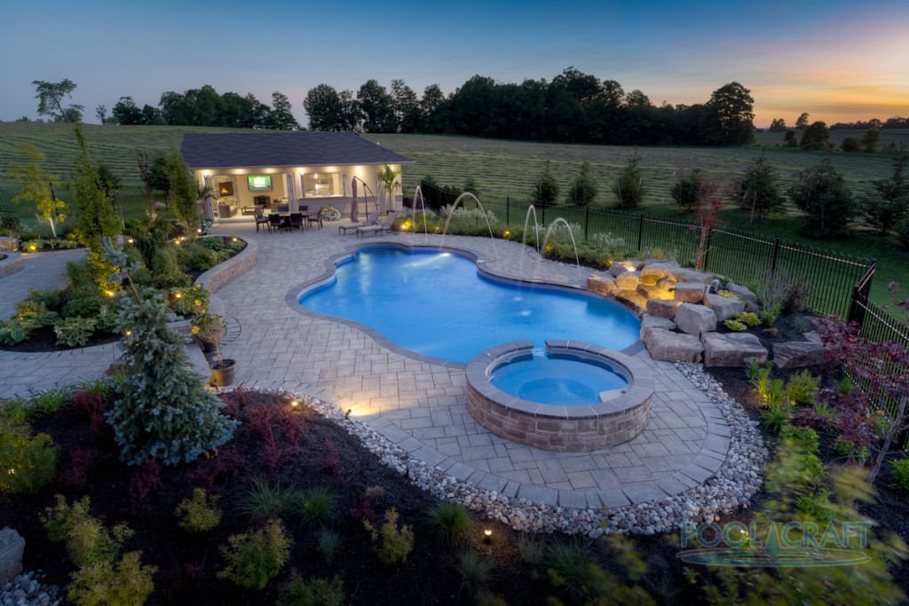 An aerial view of this home's custom pool with a jacuzzi surrounded by beautiful plants and flowers.