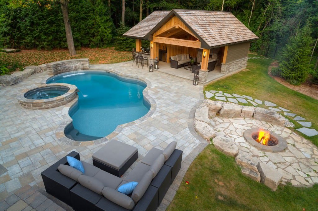 A freeform swimming pool with a poolside house and fire pit along with an outdoor seating area offering a V-shaped sectional sofa that's paired with a gray ottoman.