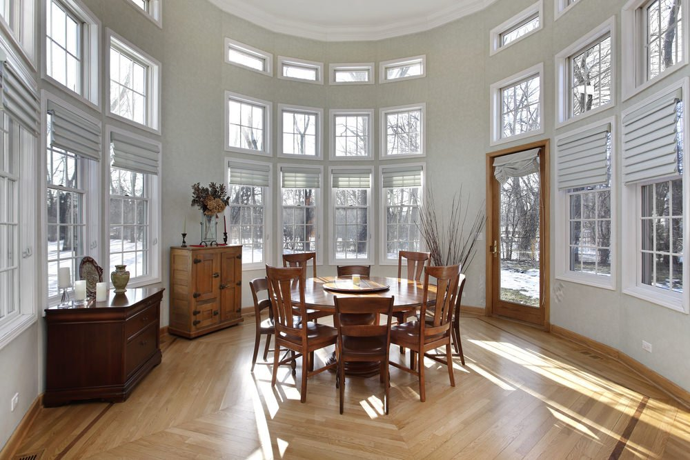 A transitional sunroom with a high ceiling, wooden furniture and dirty white walls.