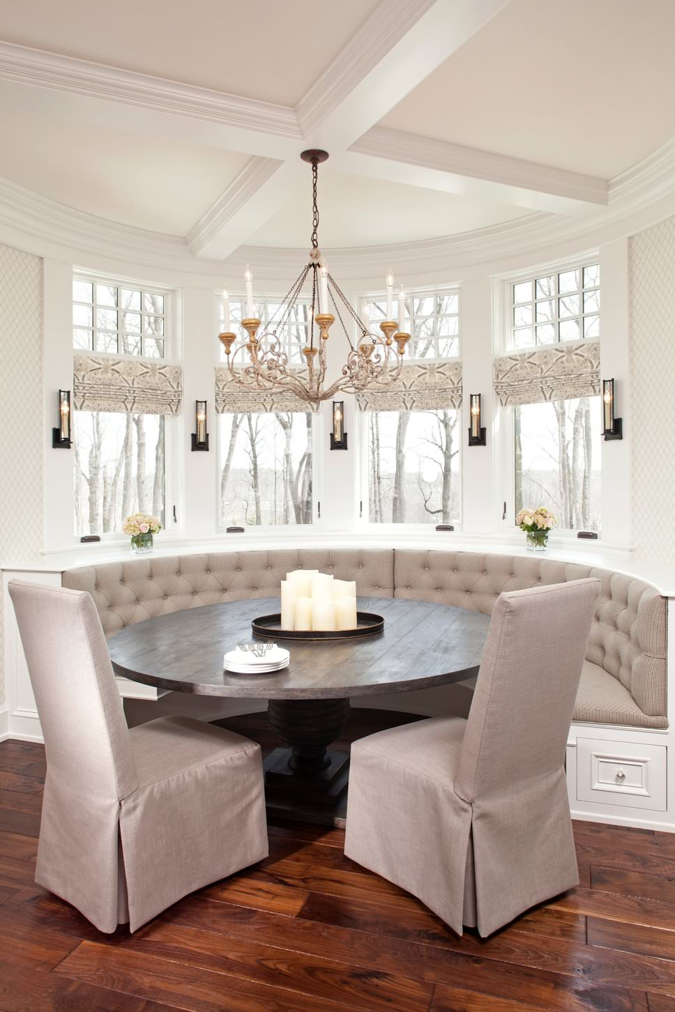 Elegant dining nook boasts a gray tufted built-in seating along with a wooden dining table and skirted high back chairs that are illuminated by candle sconces and a classy chandelier that hung from the round coffered ceiling.