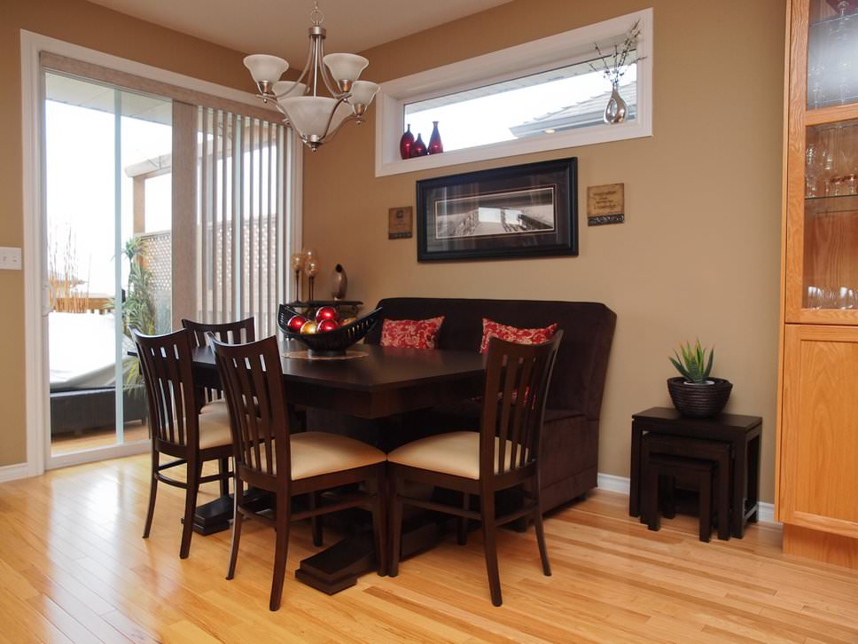 Warm dining nook offers a dark wood dining table surrounded with beige cushioned chairs and a brown sofa topped with red pillows.