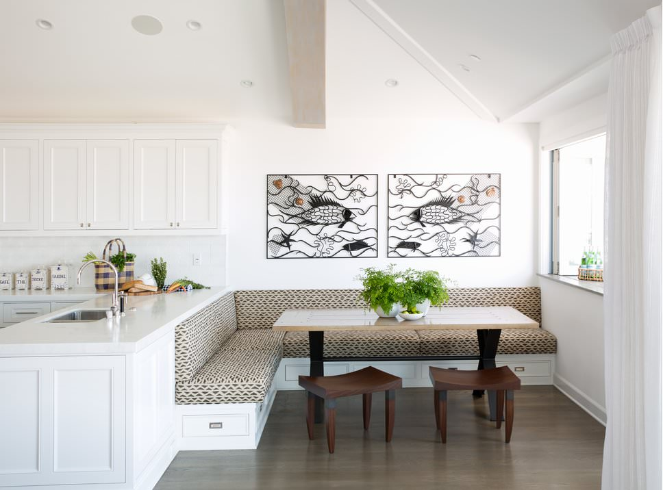 White dining nook decorated with lovely fish wall arts that hung above the built-in seating fixed to the white peninsula and fitted with patterned sectional cushions.