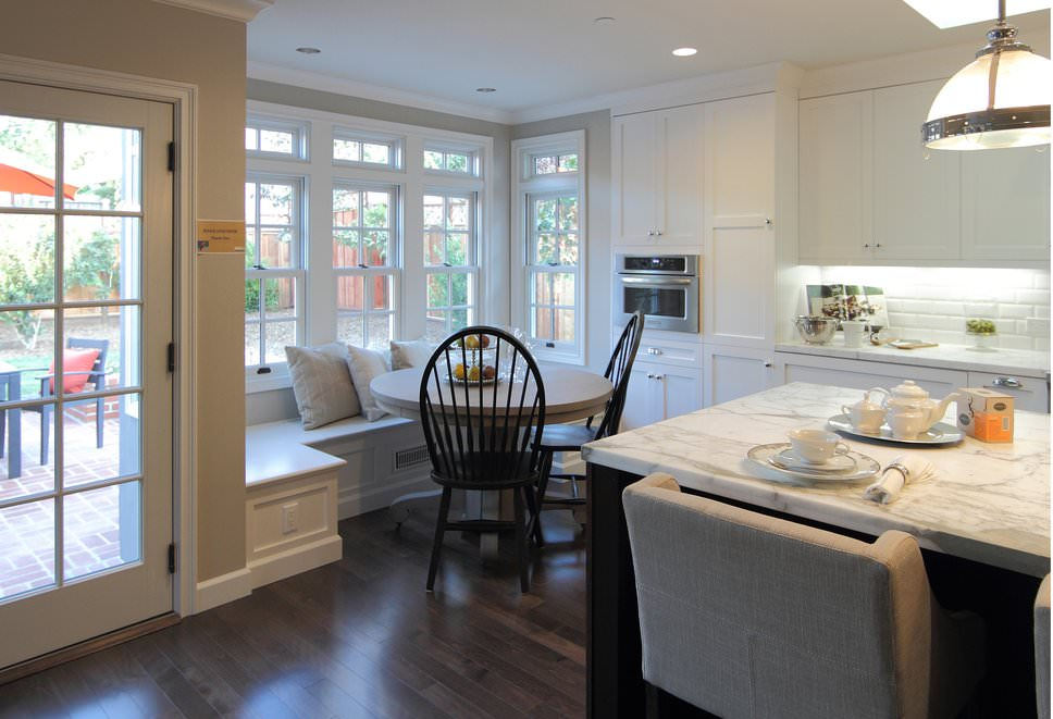 This dining nook is situated in the corner of the kitchen and by the glass windows overlooking the outdoor view. It has white built-in seating along with a wooden dining table and black round back chairs.