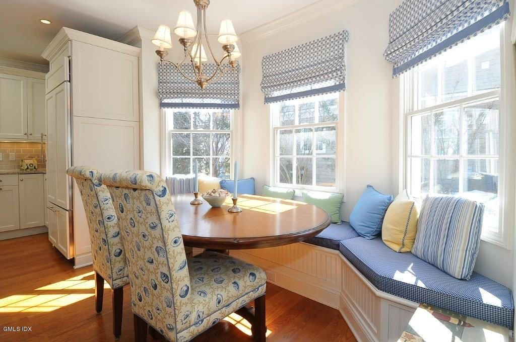 Charming dining nook with hardwood flooring and triple windows covered with blue dotted roman shades. It has a round dining table paired with high back chairs and white built-in bench lined with sectional cushions and pastel pillows.