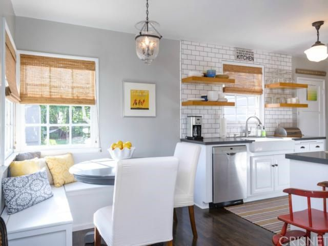 Sleek dining nook beside the kitchen with gray walls mounted with a small wall art. It also has white framed glass windows covered in wicker roman shades.
