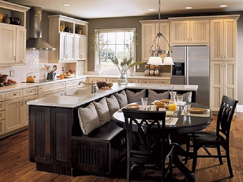 A dark wood dining nook with gray pillows is attached to the island bar maximizing the space in this kitchen with white beadboard cabinetry.