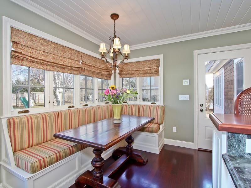 Classic dining nook with white built-in bench fitted with striped cushions and sits below the glass windows covered with floral roman shades. It is accompanied by a rich wood dining table that complements with the hardwood flooring.