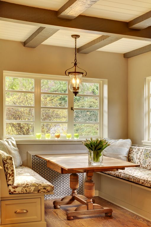 A glass pendant light that hung from the wood beam ceiling illuminates this dining nook boasting a wooden dining table and built-in chairs with floral patterned cushions.