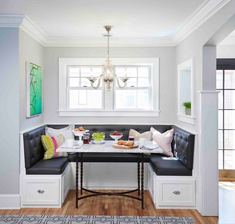 Elegant breakfast nook showcases a black tufted built-in seating paired with a black metal dining table that's illuminated by a classy chandelier.