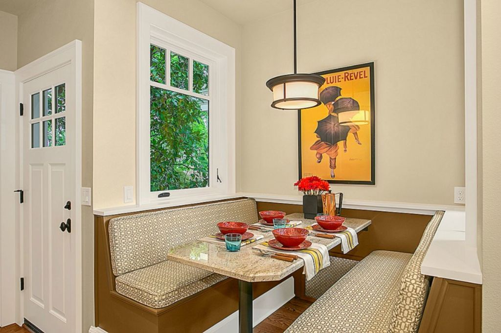 Beige breakfast nook designed with a yellow wall art that's mounted above the marble top dining table in between matching built-in benches.